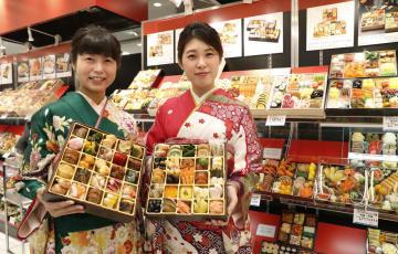 近鉄百貨店本店でおせち料理の店頭予約受け付けが始まり、見本を手にする着物姿の従業員=19日午前、大阪市