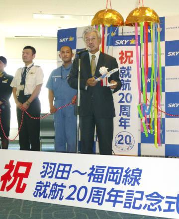 就航20周年の記念式典であいさつするスカイマークの佐山展生会長=19日午前、羽田空港