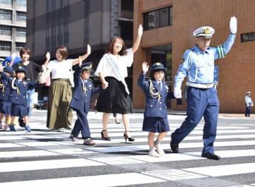 早川本部長(右)らと手を上げて横断歩道を渡る園児=18日、県警本部前交差点