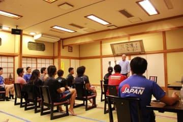 辻さんの講義を受ける選手とスタッフ