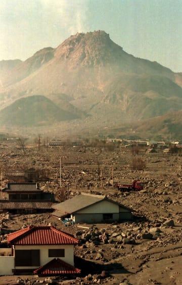 山頂火口直下を震源とする火山性地震が多発する雲仙・普賢岳。手前は土石流で埋まった家屋