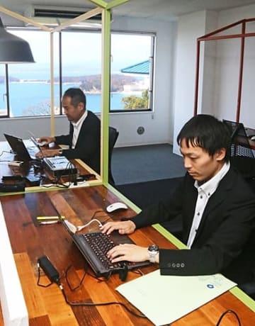 【海を望むITビジネスオフィスの一室で仕事をする内閣府の職員(18日、和歌山県白浜町で)】