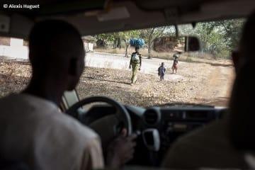 武装勢力の攻撃を逃れ、徒歩で避難する母子
