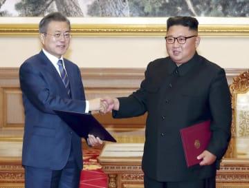 平壌の百花園迎賓館で署名した「9月平壌共同宣言」を手に握手する韓国の文在寅大統領(左)と北朝鮮の金正恩朝鮮労働党委員長=19日(平壌写真共同取材団・共同)