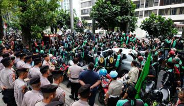 グラブ本社が入居するオフィスビル前で、所属するバイクタクシーの運転手がデモを繰り広げた=19日、ジャカルタ(NNA撮影)