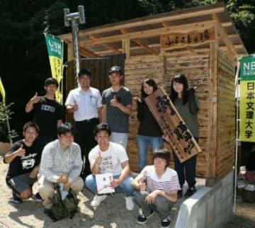 五右衛門風呂の建屋の前でポーズを取る学生たち=豊後大野市大野町