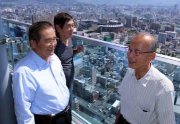 マツダスタジアムを背に地元優勝への期待を語る中村さん(左)、幾久さん(中)、平野さん