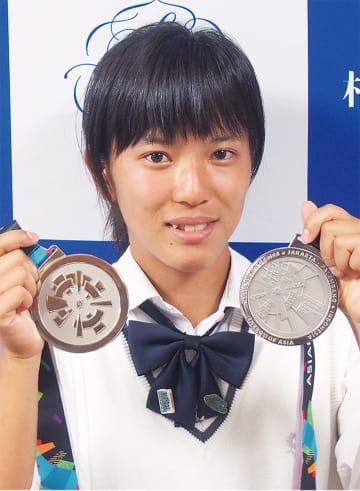 2つのメダルを手にはにかむ伊佐さん=11日、相模女子大学中学部・高等部