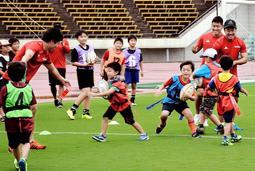 神戸製鋼の現役選手らとラグビーに触れ合う子どもたち=神戸市須磨区緑台、ユニバー記念競技場
