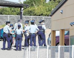 刺殺事件があった東仙台交番(右)裏に集まる警察官=19日午前11時40分ごろ