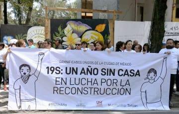 昨年9月の地震犠牲者を悼む式典で、横断幕を広げて住宅再建などを訴える住民ら=19日、メキシコ市(共同)
