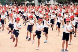 姿勢を意識し、片足でバランスを取りながら手を上げる児童ら=神戸市東灘区住吉東町4