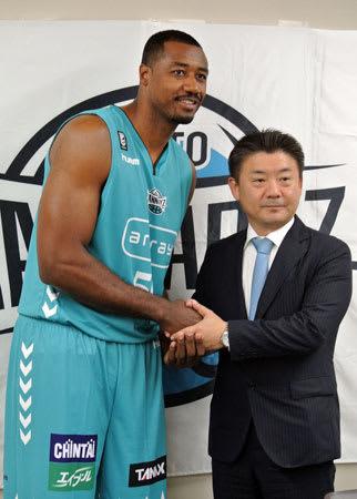 京都の高田社長(右)と握手を交わす新加入のサイモン(横大路体育館)