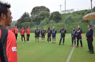 サンガの選手やスタッフを前に激励の言葉を掛ける府サッカー協会の村山会長(右端)=東城陽グラウンド