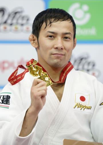 柔道世界選手権の男子60キロ級で獲得した金メダルを手に笑顔の高藤直寿=20日、バクー(共同)