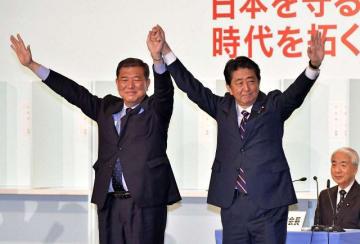 両院議員総会で健闘をたたえる声援に応える安倍氏(右)と石破氏=自由民主党本部8階ホール