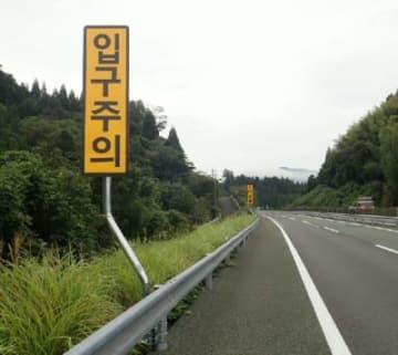 大分自動車道下り線の玖珠サービスエリア入り口近くに設置された外国語看板。手前が韓国語、奥が中国語で注意を促している(西日本高速道路提供)