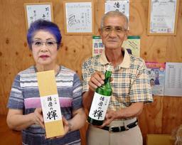 自ら生産した山田錦で醸造した大吟醸酒「播磨の輝」を持つ井上実さん(右)と芳子さん=加東市西古瀬
