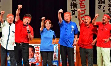 ガンバロー三唱で気勢を上げる松川正則氏(右から3人目)ら=20日、宜野湾市民会館
