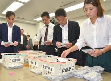 自民党総裁選の党員投票の開票作業に当たるスタッフら=20日、大阪市中央区