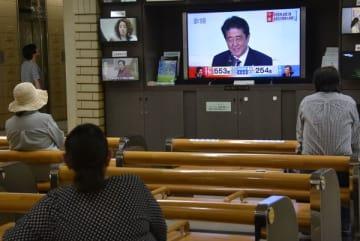 安倍首相の連続3選を伝えるテレビ映像を見る人たち=20日午後2時20分、宇都宮市役所