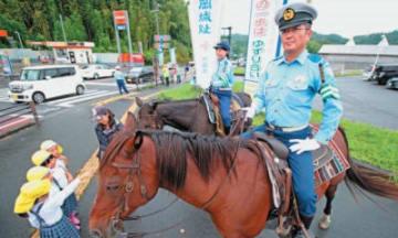 馬に乗って安全運転を呼び掛ける竹田署員=21日午前、竹田市飛田川