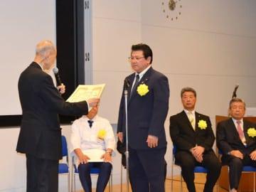 【賞状を受け取る野村社長(右)=東京都江東区の東京ビッグサイトで】