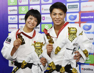 柔道の世界選手権で優勝を果たし、金メダルを手にポーズをとる男子66キロ級の兄、阿部一二三(右)と女子52キロ級の妹、阿部詩=21日、アゼルバイジャンのバクー(共同)
