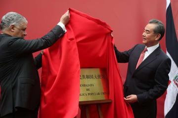 ドミニカ共和国に開設した中国大使館の表札を除幕する中国の王毅国務委員兼外相(右)=21日、サントドミンゴ(ロイター=共同)