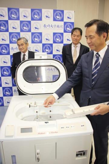 洗浄装置の使い方を説明する永安医学部長=長崎市坂本1丁目、長崎大学病院