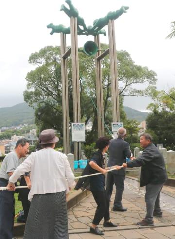 平和を願って長崎の鐘を鳴らす被爆者ら=長崎市、平和公園