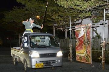 馬に見立てた軽トラックで走行し、矢を射る練習に励む流鏑馬射手会のメンバー=阿蘇市
