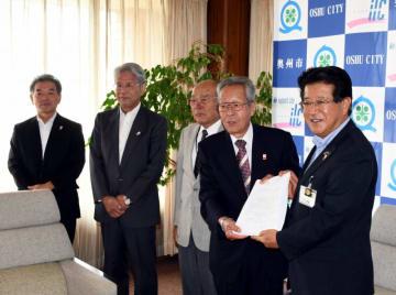 小沢昌記市長(右)に署名を提出する菊池誠会長(右から2人目)ら