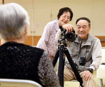 モデルに声を掛けながら写真撮影をする福盛田弘さん、美奈子さん夫妻
