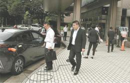 PHVの警察車両から信号機に給電するデモンストレーションを見学する青森県警などの警察官ら=11日、宮城県警本部