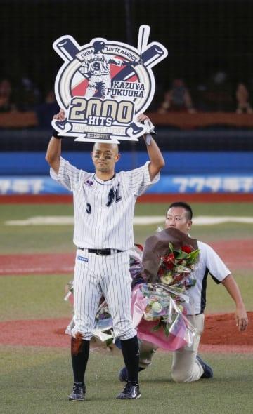 プロ野球西武戦で通算2千安打を達成し、記念のボードを掲げるロッテの福浦和也内野手=22日、千葉市のZOZOマリンスタジアム