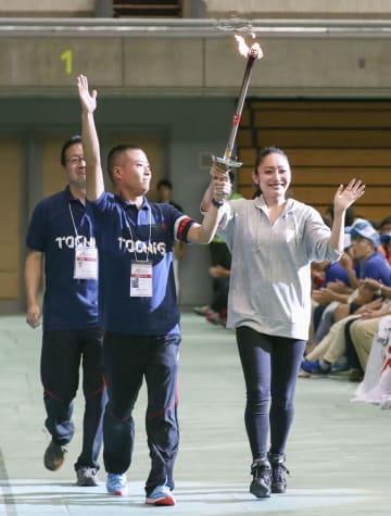 「スペシャルオリンピックス」国内大会の開会式で、安藤美姫さん(右)と聖火をリレーする選手=22日午後、名古屋市