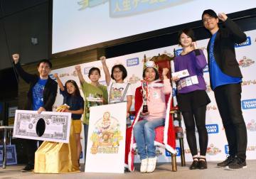 「人生ゲーム」の発売50周年を記念して行われた大会で日本一になった柴崎和美さん(右から3人目)ら参加者=22日午後、東京都千代田区