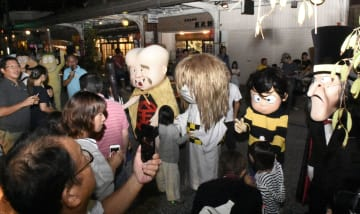 「水木しげるロード」で妖怪の着ぐるみと記念撮影する人たち=22日夜、鳥取県境港市