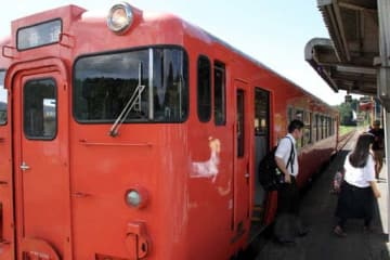 周南市の勝間駅で、再開した岩徳線の列車から降りる乗客(22日午前11時41分)