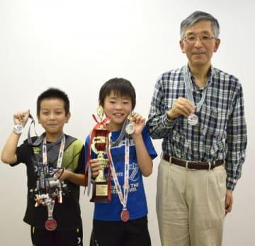 メダルとトロフィー、自作のロボットを手に笑顔を見せる原悠惺君(左)と横内蒼士君(中央)、コーチの深谷健一さん