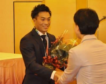 地元後援会主催の祝賀会で花束を受け取り、笑顔を見せる太田忍選手(左)=22日、五戸町のアピル五戸