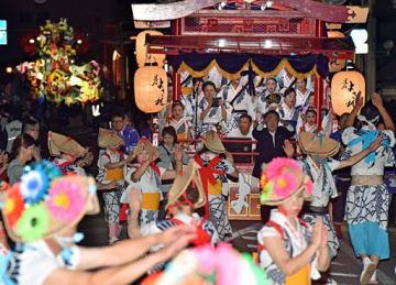 見物客を巻き込んで盛り上がった黒石よされ「廻(まわ)り踊り」。左奥は八戸三社大祭=22日夜、青森市新町
