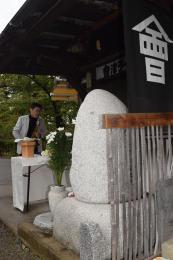 慰霊碑の前で演奏する木村さん