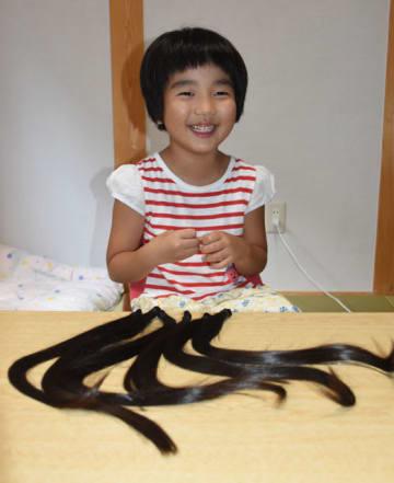 小児用の医療かつらを作ってもらうために髪の毛を切った那須夏帆ちゃんと、31センチの長さにカットされた髪の毛