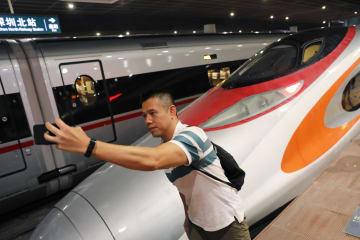 営業運転を開始した広深港高速鉄道の車両のそばでポーズを取る乗客=23日、広東省深セン(AP=共同)