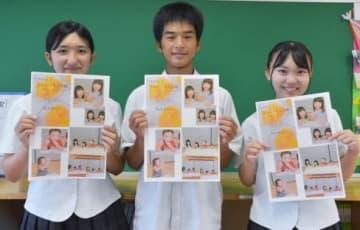 新聞「たねがしまおいしいもの広場」を手にする(写真左から)迫田栞さん、西園瑞輝さん、永浜麻里亜さん=中種子町野間の種子島中央高校