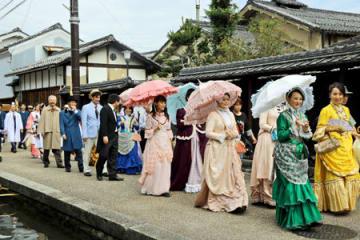 明治、大正時代の衣装を再現した紳士服やドレスなどを着て行進する参加者たち(東近江市五個荘金堂町)