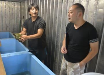 養殖場の視察に訪れた内山英仁社長(右)に温泉で育ったスッポンについて説明する甲地慎一社長=8月、七戸町李沢