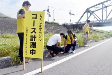 とくしまマラソンのコースを測定する実行委のメンバーら=徳島市の吉野川橋北詰め